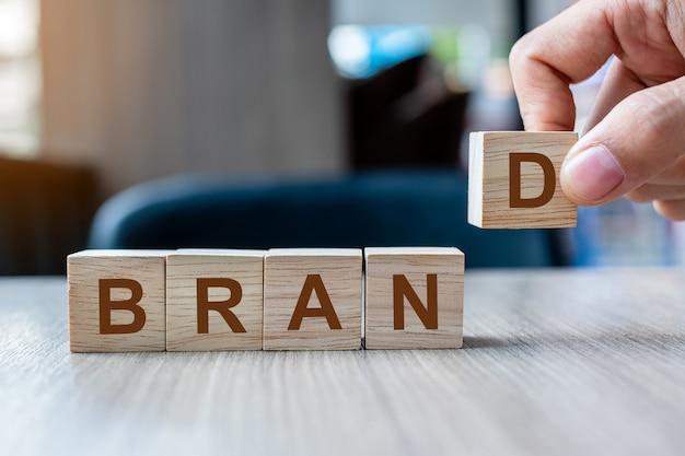 Mão do homem de negócios que guarda o bloco de madeira do cubo com palavra do negócio do marca no fundo da tabela.