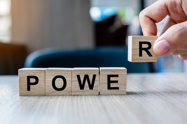 Mão do homem de negócios que guarda o bloco de madeira do cubo com palavra do negócio do poder. palavras têm conceito de poder