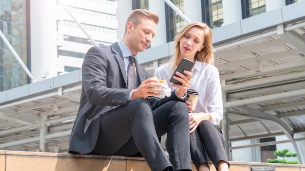 Mão do homem de negócios que guarda o fast food do hamburger e que olha o telefone que senta-se em urbano exterior. com mulher de negócios.