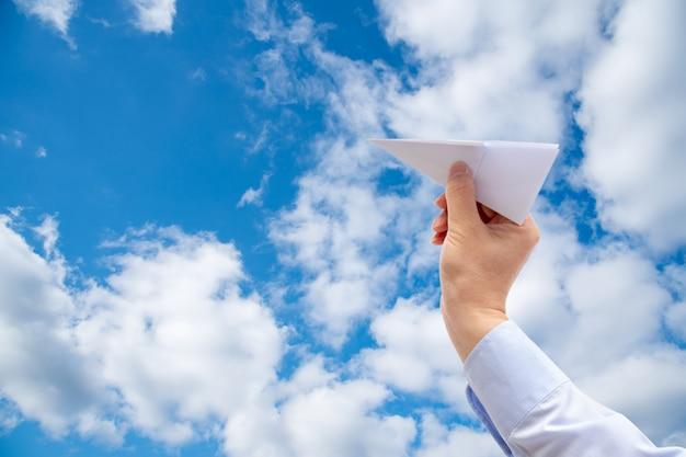 Mão do homem de negócios que guarda o plano de papel no céu.