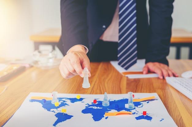 Mão do homem de negócios que joga a xadrez com mapa do mundo como uma placa. conceito de estratégia de negócios.