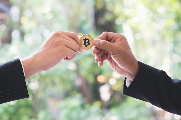 Mão do homem de negócios que passa a moeda dourada do bitcoin do cryptocurrency no escritório.