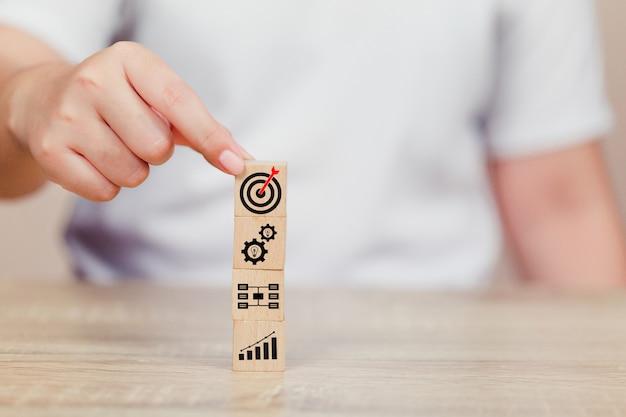 Mão do homem de negócios que põe o bloco de madeira do cubo na parte superior com conceito do sucesso do alvo.