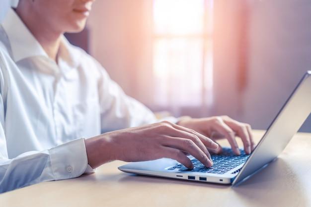 Mão do homem de negócios usando o laptop no escritório.