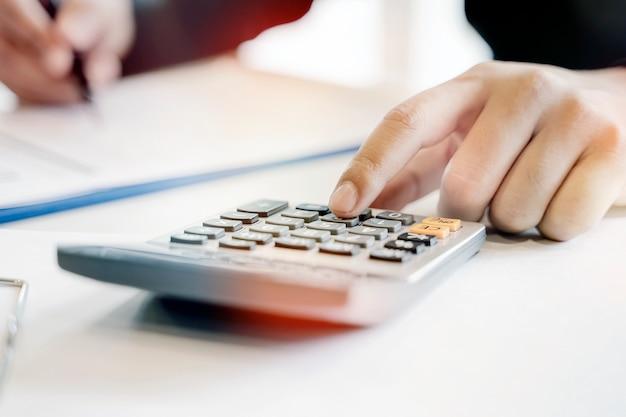 Mão do homem do close up usando a calculadora ao sentar-se na mesa de escritório.
