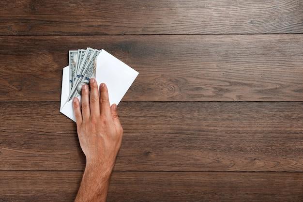 Mão do homem e dólares dos eua em um envelope branco