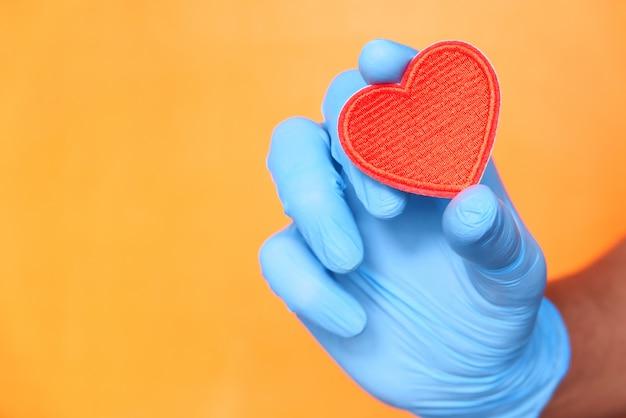 Mão do homem em luvas protetoras segurando coração vermelho.