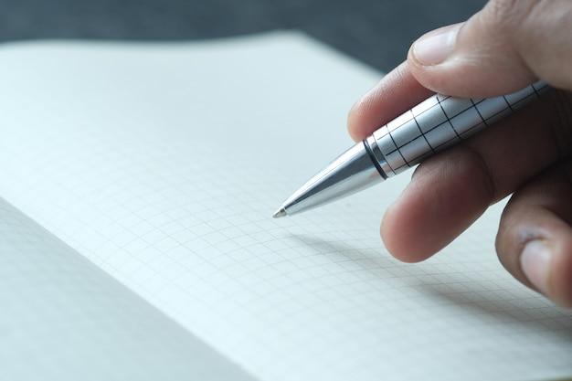 Mão do homem escrevendo com caneta no papel