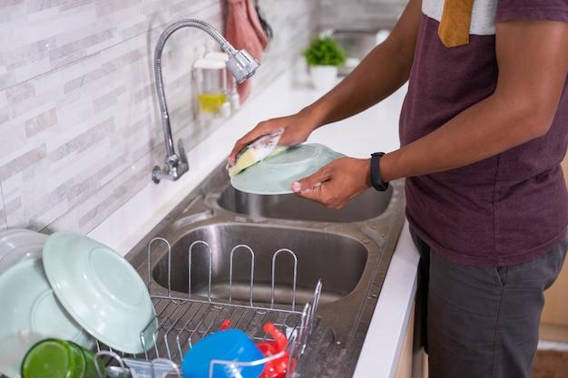 Mão do homem lavar o prato na pia da cozinha
