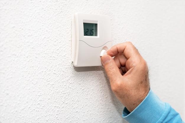 Mão do homem que ajusta o termostato em casa. escala de temperatura celsius.
