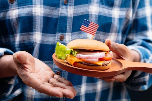 Mão do homem que guarda o hamburguer caseiro americano.