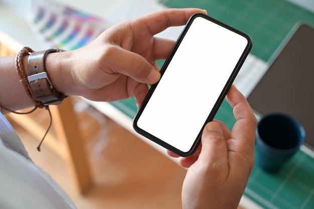 Mão do homem que guarda o telefone esperto móvel da tela vazia no local de trabalho.