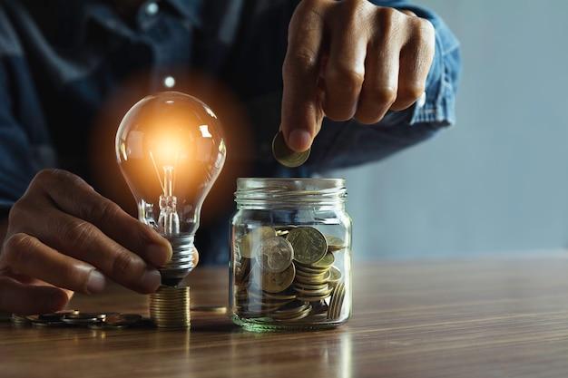 Mão do homem que guarda uma ampola com dinheiro das moedas e espaço da cópia para a contabilidade, as ideias e o conceito criativo.