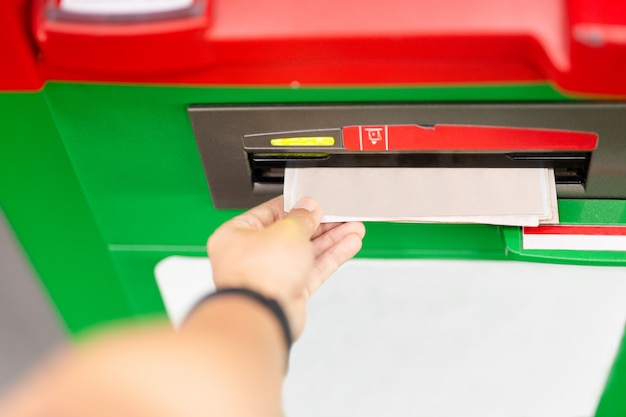 Mão do homem que usa uma máquina do atm com cartão de crédito.