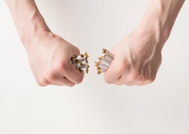 Mão do homem, quebrando o monte de cigarros sobre o pano de fundo branco