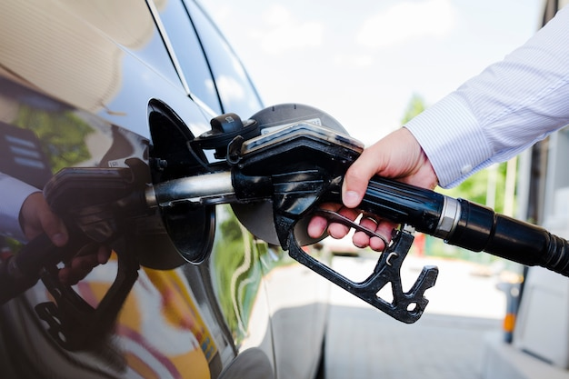 Mão do homem, reabastecimento de carro no posto de gasolina
