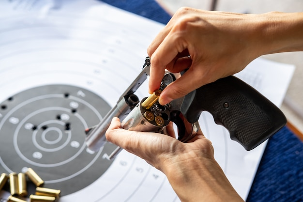 Mão do homem recarregando o revólver de pistola com balas e alvo