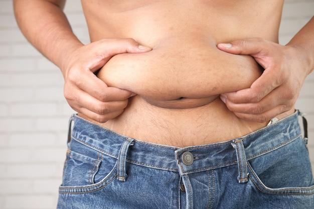 Mão do homem segurando conceito de excesso de peso na barriga