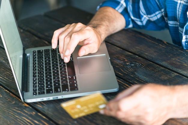 Mão do homem segurando o cartão de crédito, digitando no laptop sobre a mesa de madeira