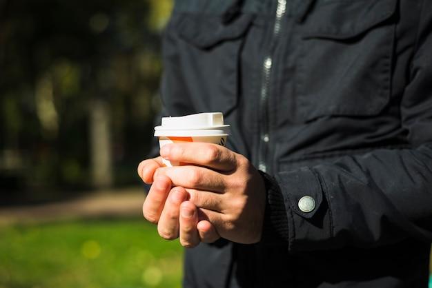 Mão do homem segurando o copo de café descartável