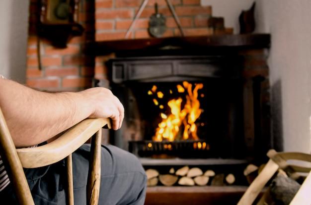 Mão do homem sentado na cadeira de balanço em frente a lareira em casa
