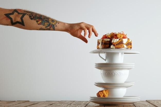 Mão do homem tatuado estendendo-se para pegar um pedaço de bolo equilibrado na pirâmide de utensílios de chá brancos