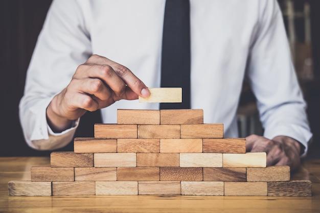 Mão do homem tem acumulando e empilhando um bloco de madeira, plano e estratégia em negócios