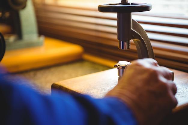 Mão do horologista usando um microscópio