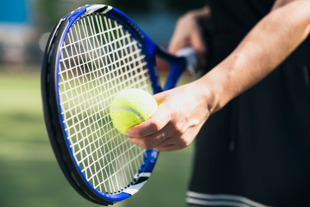 Mão do jogador com bola de tênis e raquete
