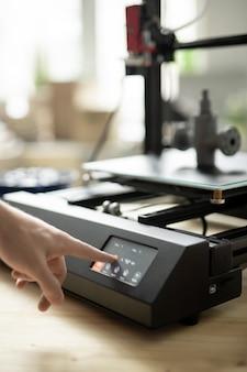 Mão do jovem designer pressionando o botão iniciar no painel de controle da impressora 3d antes de iniciar o processo de trabalho