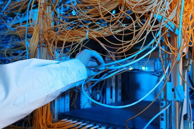 Mão do jovem engenheiro conectando cabos na sala do servidor