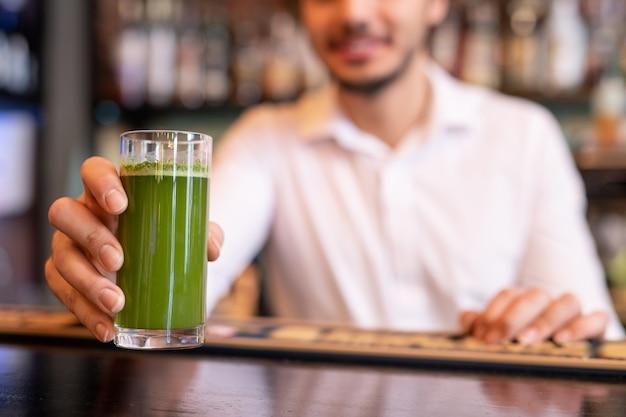 Mão do jovem garçom da cafeteria ou restaurante elegante colocando um copo de smoothie de vegetais frescos de cor verde no balcão do bar