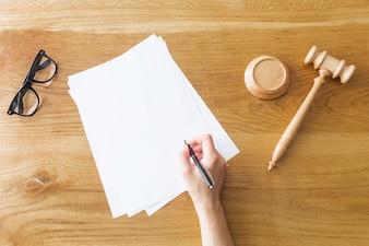 Mão do juiz, escrevendo no papel perto de martelo e óculos na mesa de madeira