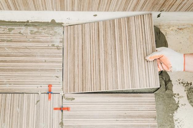 Mão do ladrilhador colocando azulejo no adesivo