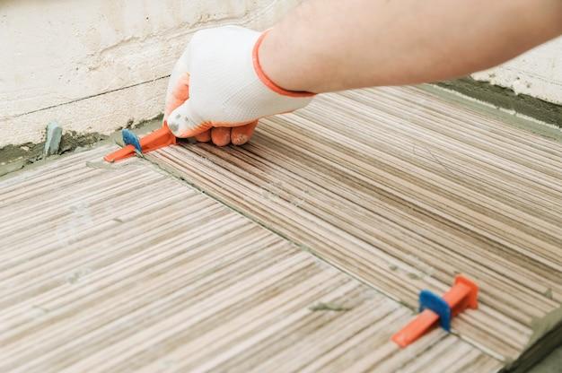 Mão do ladrilhador usando cunhas e clipes de plástico para alinhar as peças