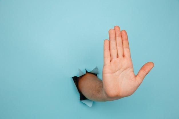 Mão do macho fazendo sinal através de um buraco no papel isolado sobre fundo azul.