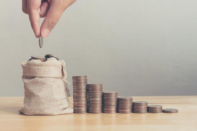Mão do macho ou da fêmea que põe moedas no saco do dinheiro com etapa da pilha da moeda crescimento crescente que conserva o dinheiro, investimento do negócio da finança do conceito