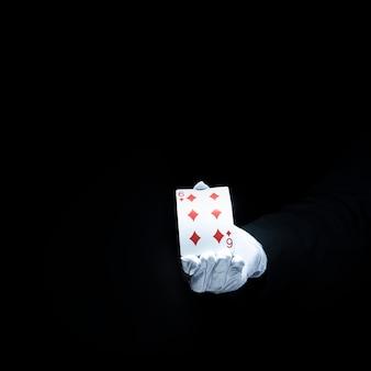 Mão do mago mostrando o cartão de jogo de diamante contra o fundo preto