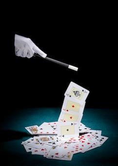 Mão do mago pegando cartas de ases com varinha mágica sobre a mesa de poker