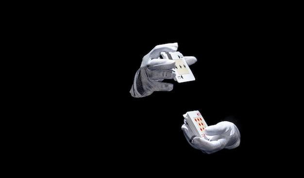 Mão do mago segurando cartas de jogar contra o fundo preto