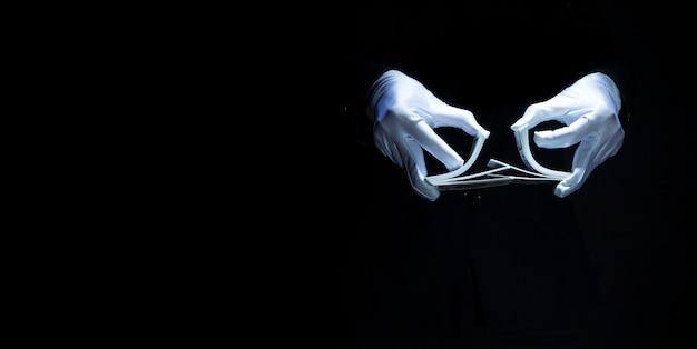 Mão do mago usando luva branca mostrando truque com cartas de baralho