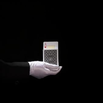 Mão do mago usando luvas brancas, realizando truque em cartas de baralho