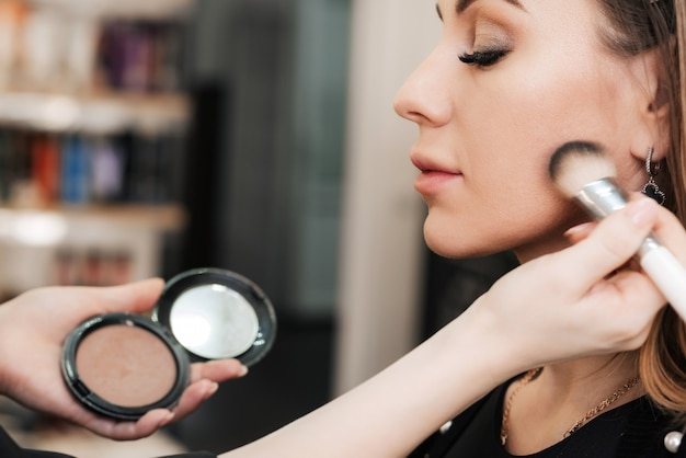 Mão do maquiador com um pincel de sombra fazendo maquiagem no rosto de uma mulher