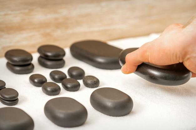 Mão do massagista colocando pedras de massagem na mesa no salão spa
