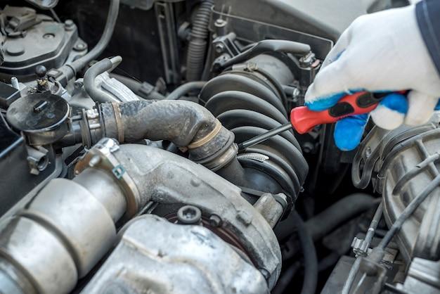 Mão do mecânico com conserto de chave de fenda ou verificação do carro na garagem