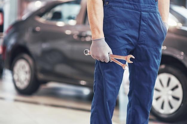 Mão do mecânico de automóveis com chave. oficina de reparação automóvel