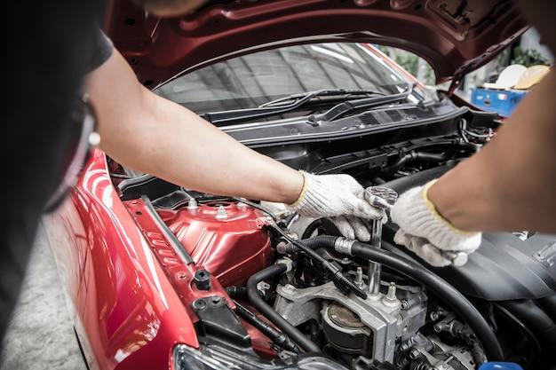 Mão do mecânico de automóveis, fazendo manutenção e serviço de carro.
