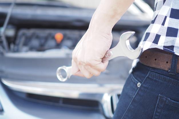 Mão do mecânico de carro com uma chave do reparo do carro.