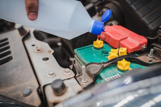 Mão do mecânico verifique e adicione água à bateria do carro, o mecânico automático de foco seletivo usa para verificar e fazer a manutenção da bateria do carro.