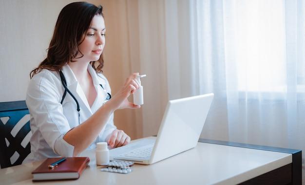 Mão do médico close-up um punhado de pílulas, medicamentos, medicamentos, comprimidos. consulta médica on-line do laptop.